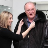 Federal fisheries minister Keith Ashfield tries on a sealskin coat on Thursday with help from Jennifer Shears, owner of NaturaL Boutique in St. John's.